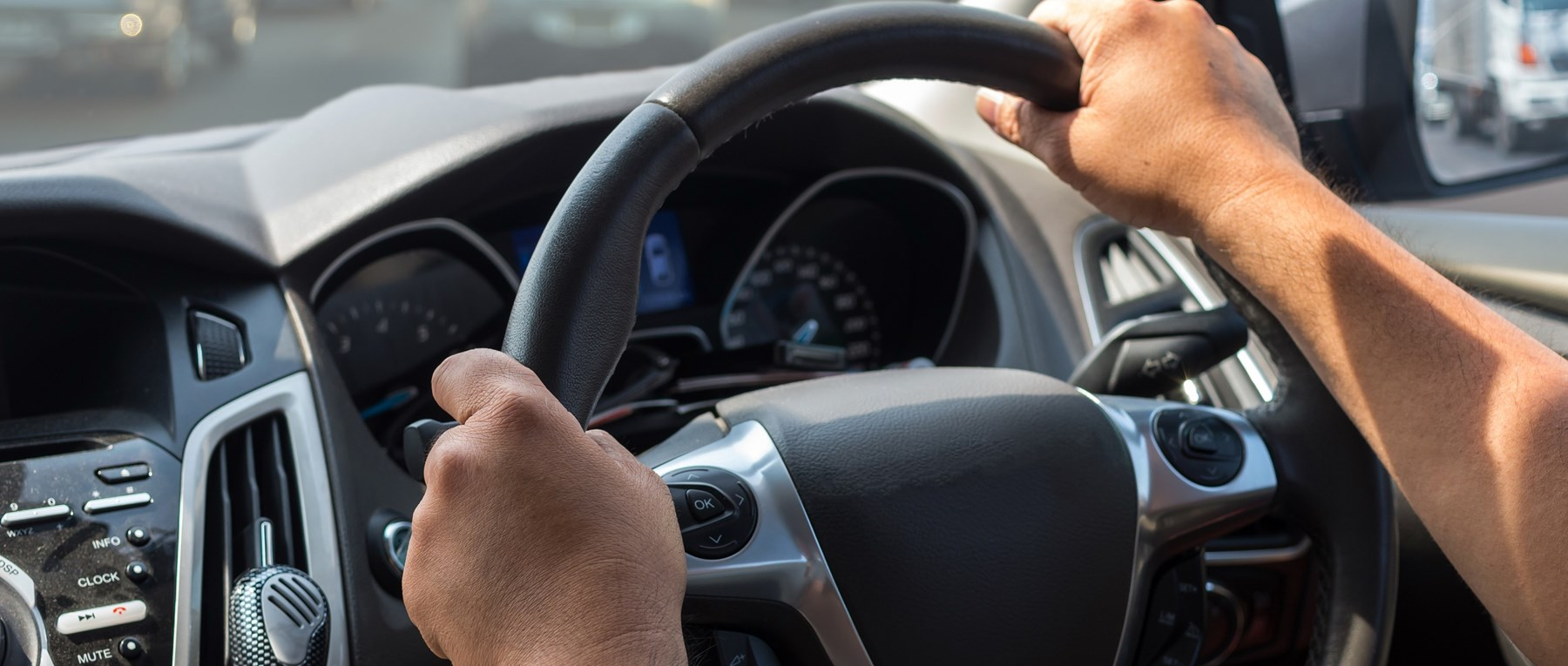 Man's arms on a steering wheel