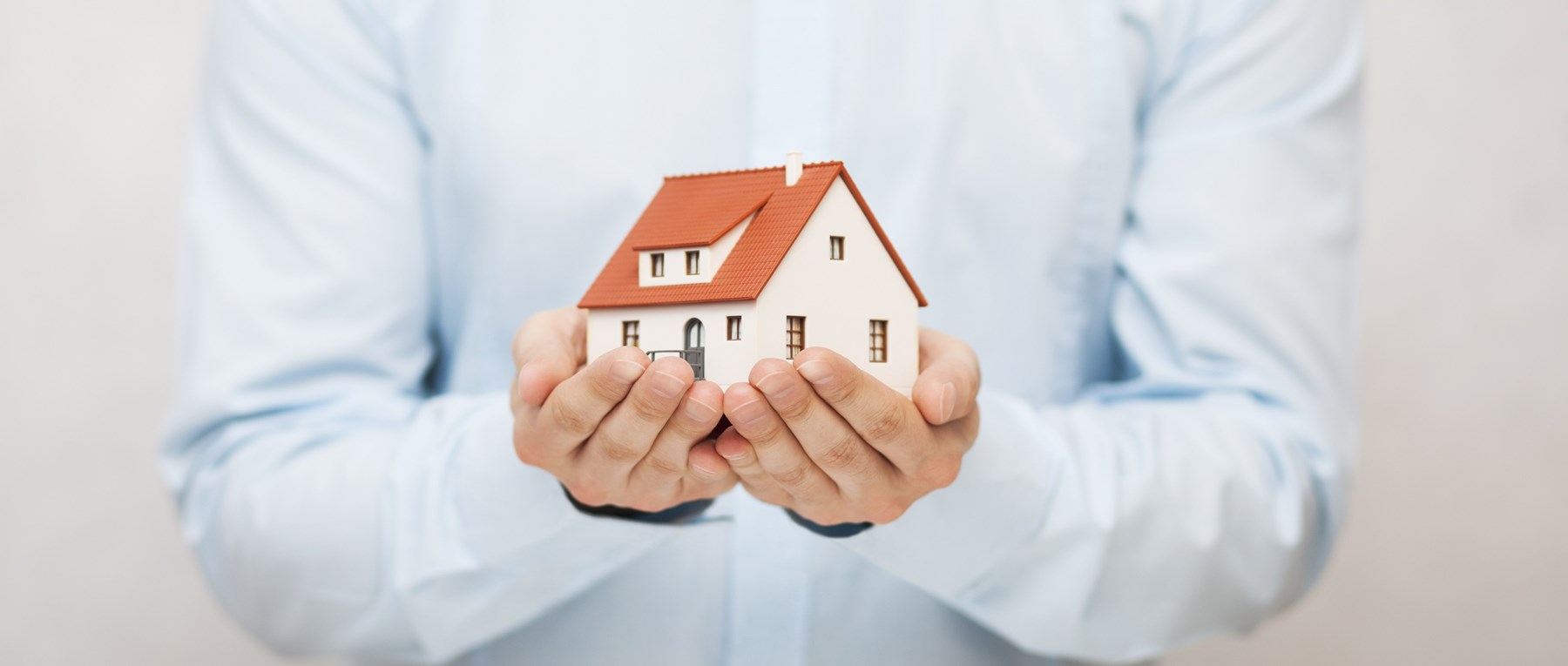 Man's hands holding model house
