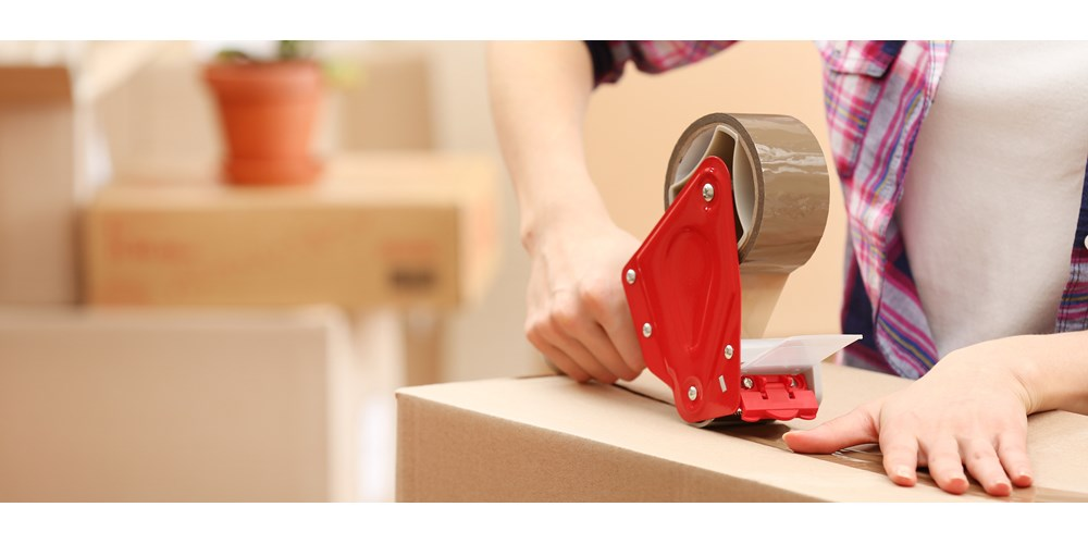 Cardboard box being taped using sellotape dispenser