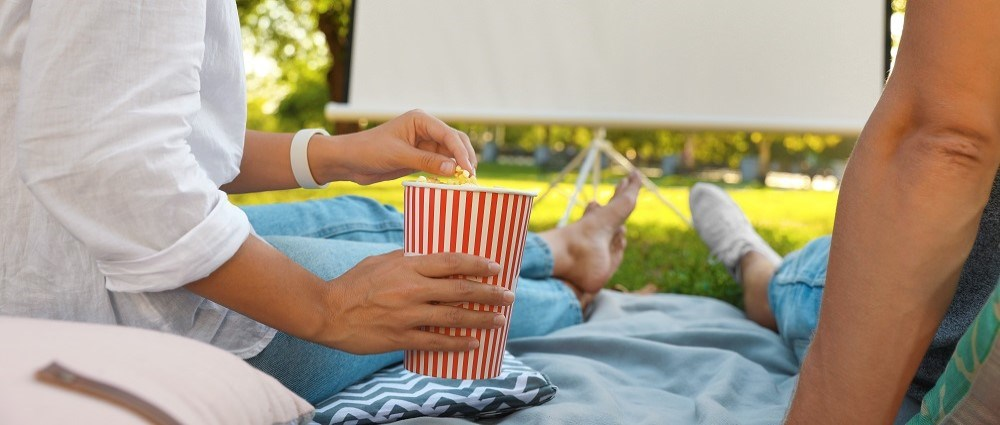 Couple getting ready to watch film outdoors