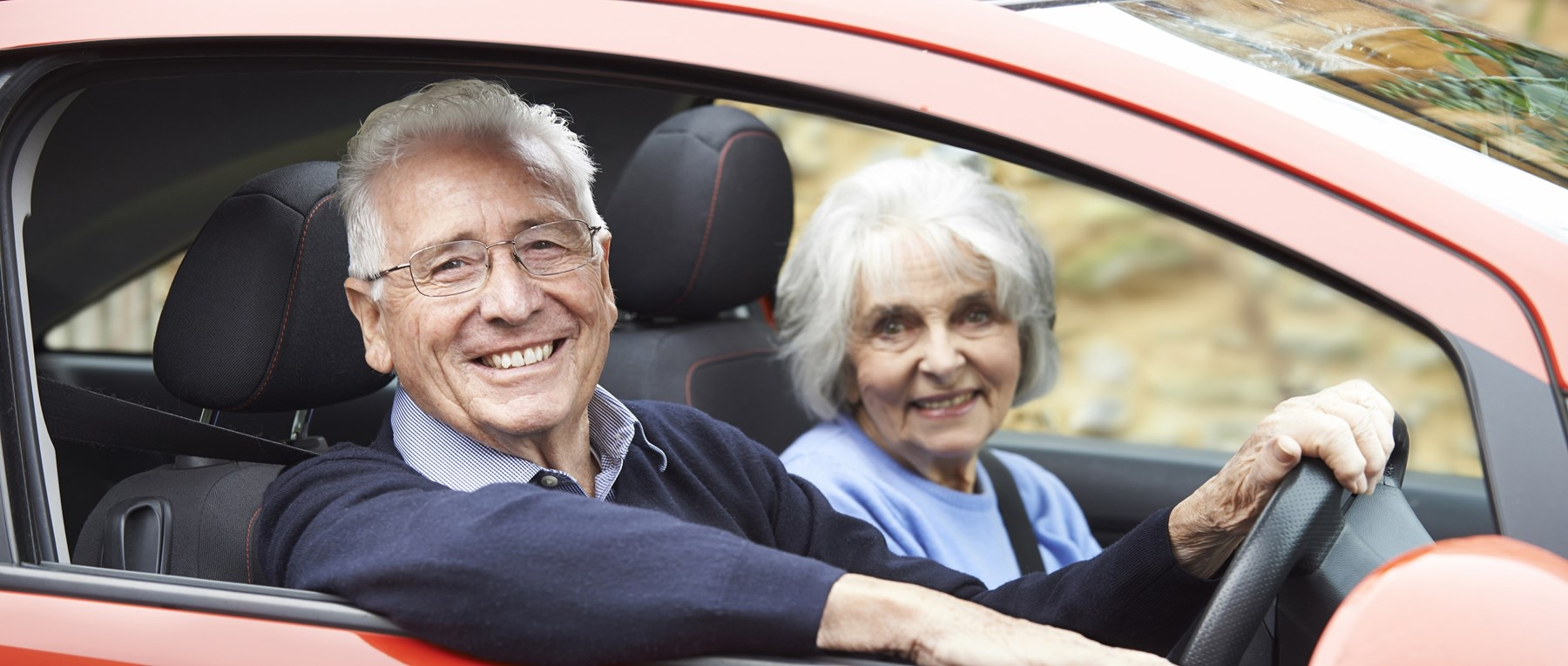 Older couple in an orange car