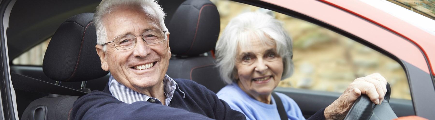 Older couple in an orange car