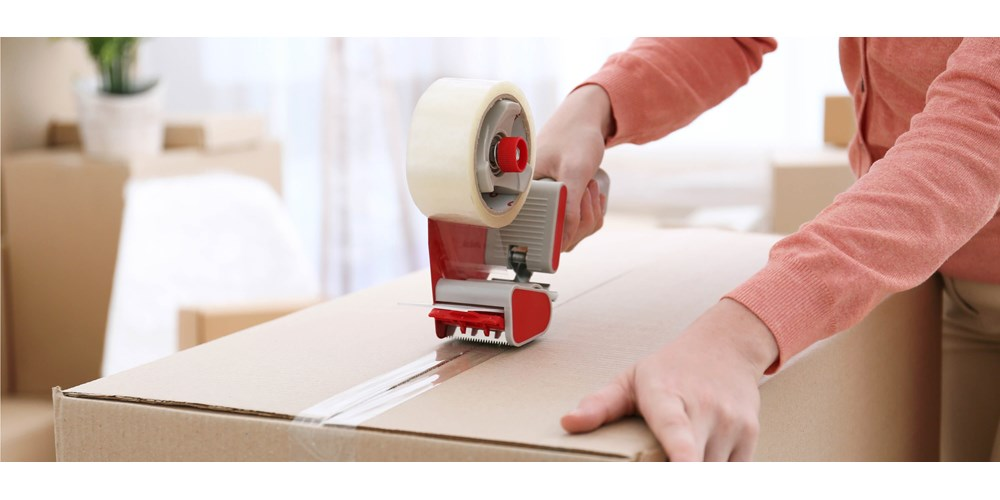 A box being taped up using sellotape dispenser