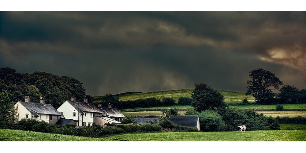 A stormy sky above houses in the countryside