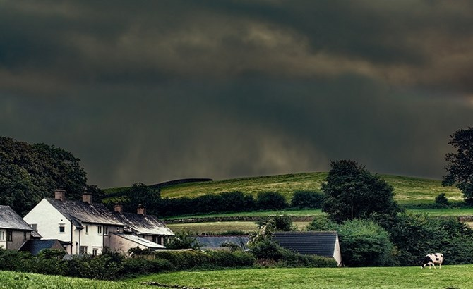 Dark cloudy sky above houses in a country area