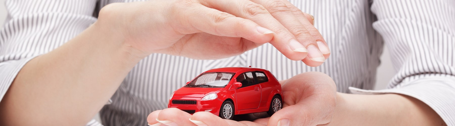 Red toy car held and covered by a woman's hands