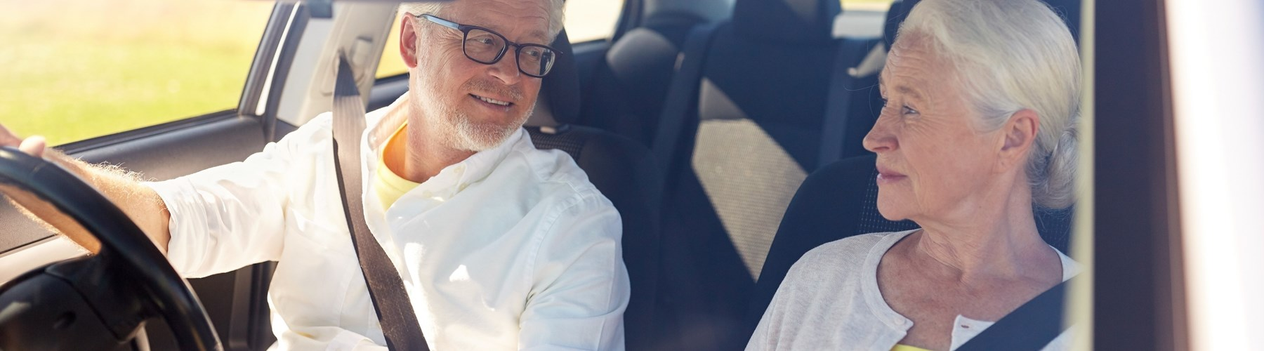 older couple smiling in car