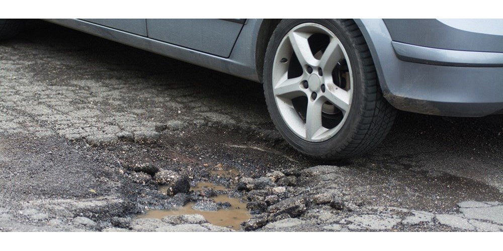 Silver car next to pothole