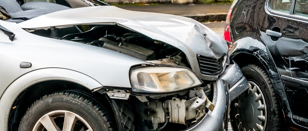 Silver car with frontal damage after crash