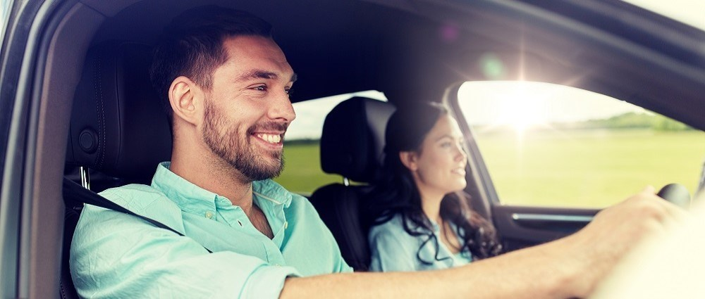 Smiley man driving car with woman in the passenger seat