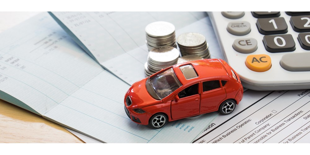 Red toy car with calculator and coins on top of documents