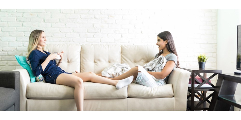 Two women talking on a cream sofa