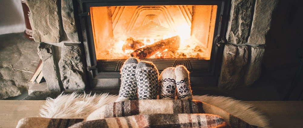 Two pairs of feet with socks on by the fire