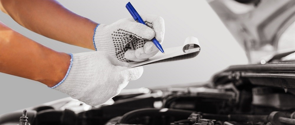 Someone making notes on a clipboard over a car engine