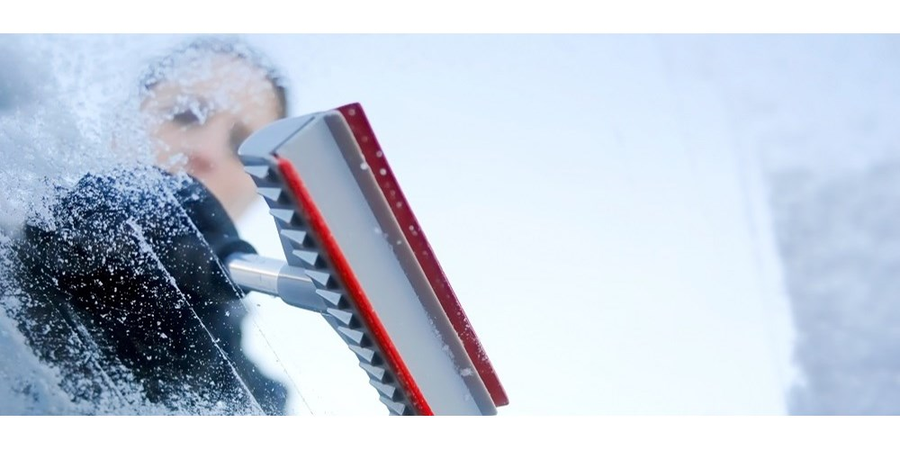 Woman scraping windscreen on snowy day