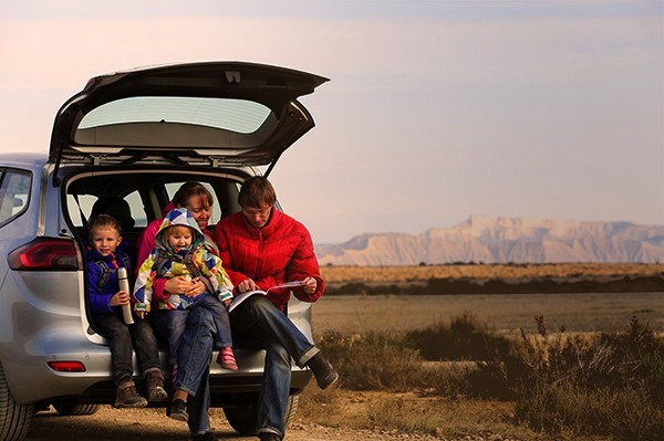 Man with children looking at boot in car boot