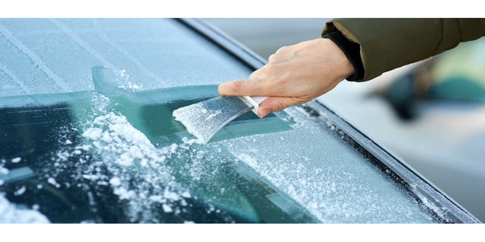 Person scraping ice of windscreen