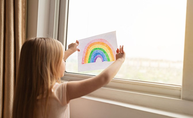 Child holding rainbow drawing at a window